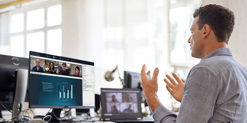 Man talking with video call participants and looking at a bar graph on his monitor.