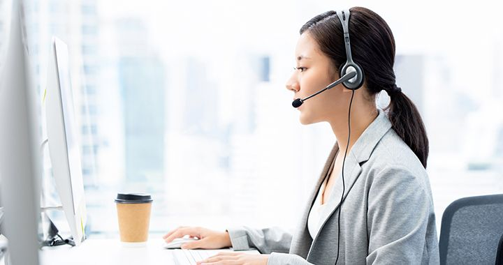 Business woman sitting in a brightly lit room talking on a headset
