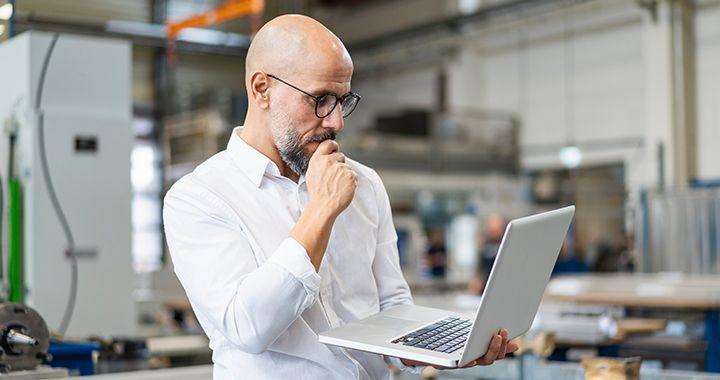 Empresario mirando una computadora portátil en su mano dentro de un almacén