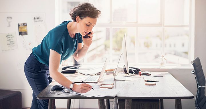Business woman standing in a brightly lit room talking on a phone while taking notes