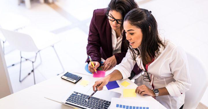 Zwei Geschäftsleute, die in einem hell erleuchteten Büroraum an einem Laptop arbeiten