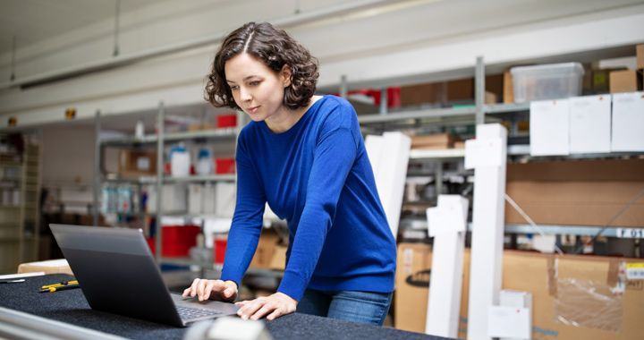 Woman in a warehouse working on a laptop
