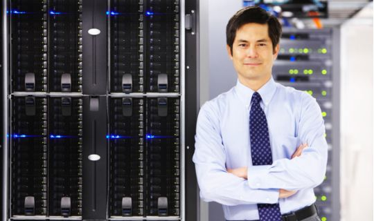 Business man leaning on a server stack next to him