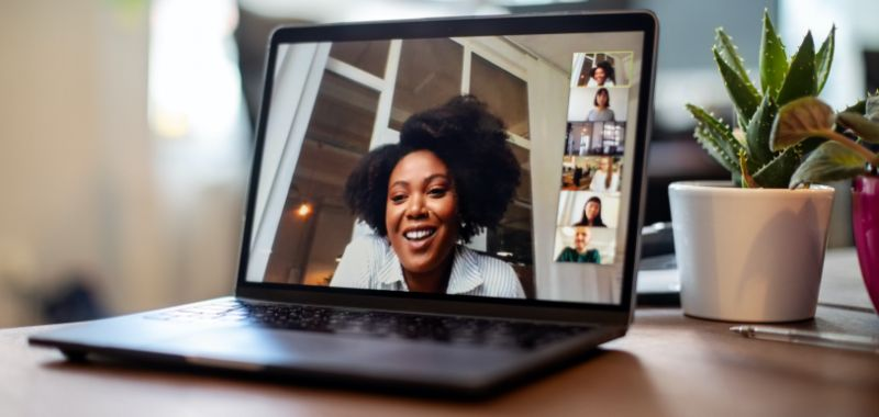 Open laptop sitting on office desk with woman displayed in centre talking in a video conference with mini-windows of people in the meeting.