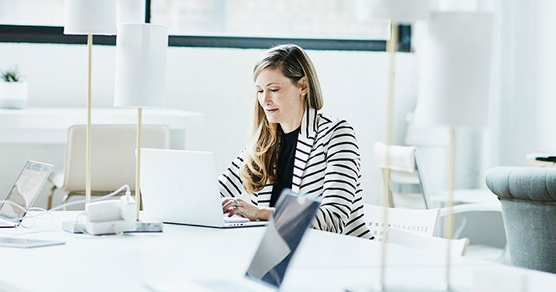 Business woman sitting in a brightly lit room working on a laptop