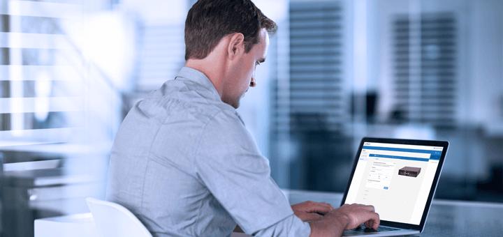 Empresario con una camisa gris trabajando en una computadora portátil en una oficina