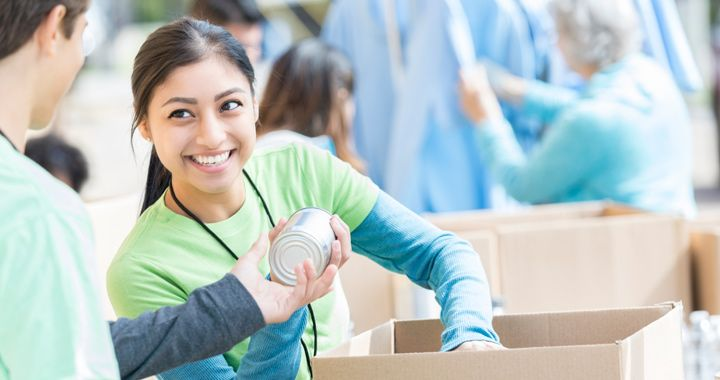 Two people volunteering and packing canned goods in front of other people in the background