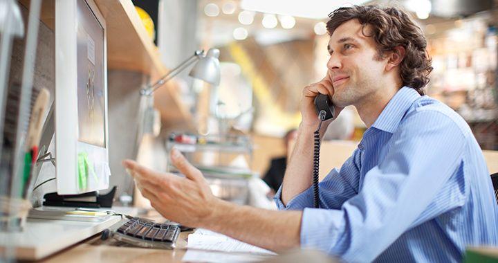 Executivo sentado em uma mesa enquanto fala no telefone