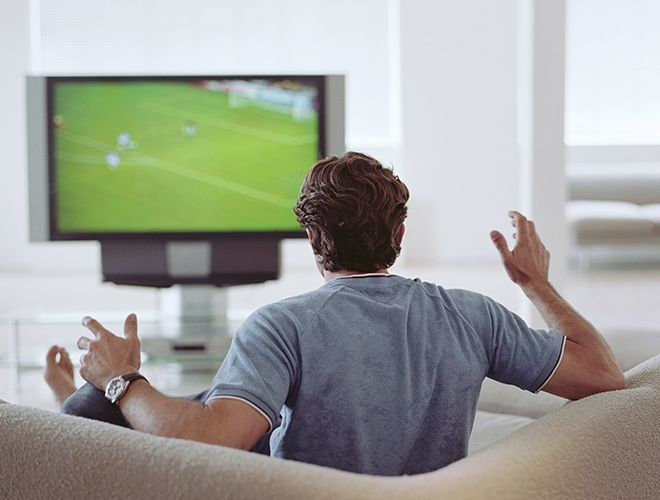 The back of a person while they watch a soccer game on TV