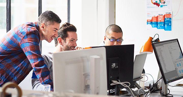 Three business men looking at computer monitors