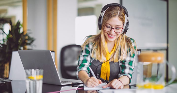 Business woman sitting in a full conference space with headphones on writing notes