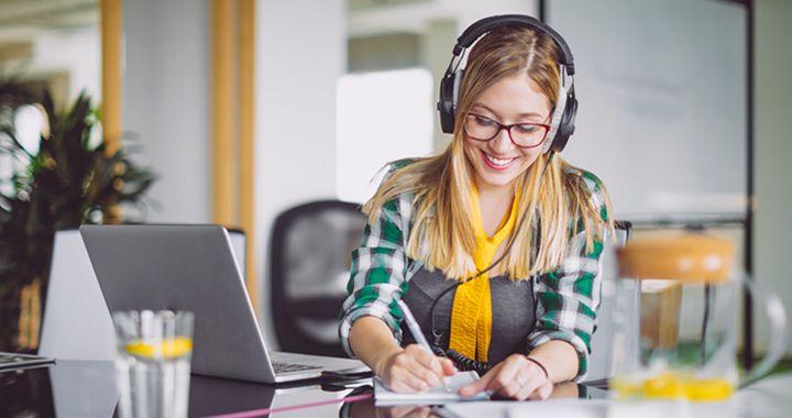 Mujer de negocios con auriculares sentada en un espacio para conferencias escribiendo notas