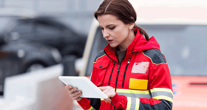 Woman in red jacket reading tablet
