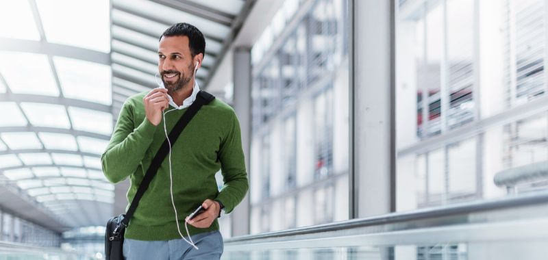 Man wearing ear buds and taking a call on his mobile phone while walking through airport.