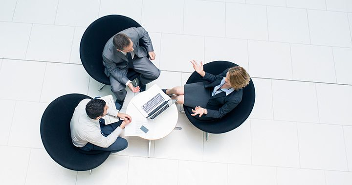 Overhead view of three business people working around a laptop
