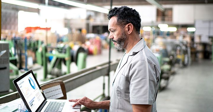 Engineer working on a laptop sitting on top of manufacturing line