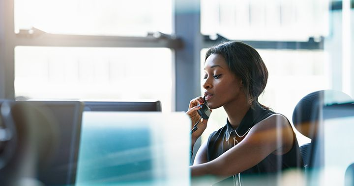 Business woman sitting in a brightly lit room talking on a phone